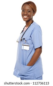 African female nurse posing casually in uniform. Hands in coat pocket
