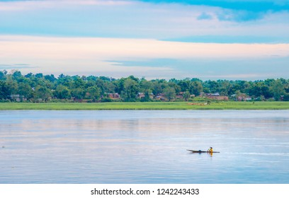 African fisherman rowing boat on Ubangi River, fishing in Bangui capital of Central African Republic. Traditional wooden boat made by African villagers