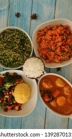 African Food on Blue Wooden Table with Plain Rice on the Center Ugali,Spinach Rice,Chicken Stew and Jollof Rice