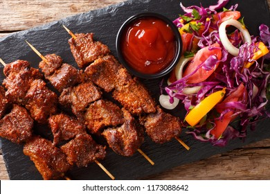 African food: spicy suya kebab on skewers with fresh vegetable salad and ketchup close-up on the table. horizontal top view from above
