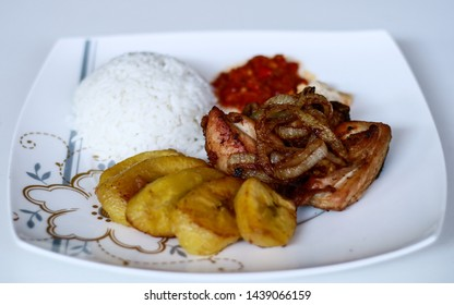 African fried chicken with fried bananas, rice, fried onions, chili sauce and candlenut sauce.