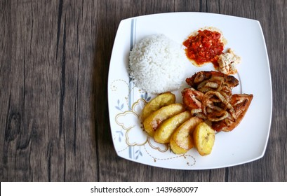 African fried chicken with fried bananas, rice, fried onions, chili sauce and candlenut sauce. Wood background.