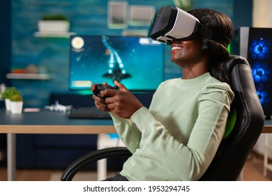 African gamer e-sports with vr sitting in chair using wireless controler. Virtual space shooter video game championship in cyberspace, esports player performing on pc during gaming tournament.