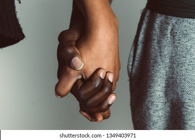African Gay, LGBT and homosexuality concept - close up of happy lesbian gay couple holding hands for love and friendship concept