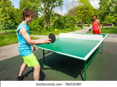 African girl and boy playing ping pong outside during summer sunny day