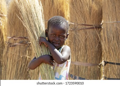 African girl child labor, in a  village in Botswana holding a broom