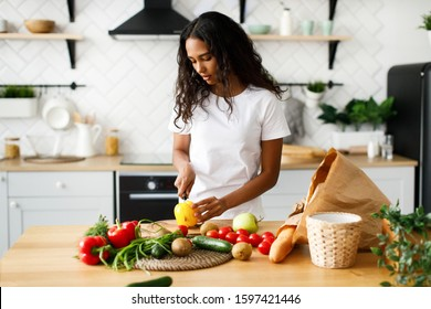 African girl is cutting a yellow pepper on the kitchen desk and on the table are products from a supermarket
