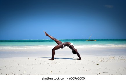 African girl doing a yoga pose on the beach