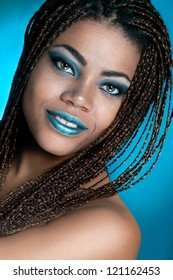 An african girl with dreadlocks and blue make up and dreads on a blue background