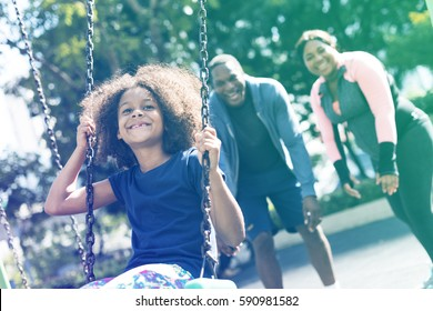 African girl having fun with swing and family