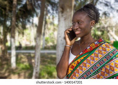 African girl in loincloth speaks on the phone while smiling