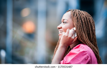 African girl outdoor talking on smartphone at city street