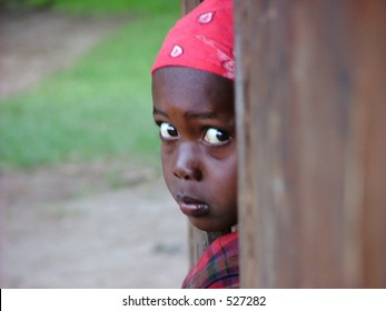 An african girl pears out of a doorway