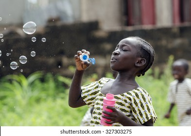 African Girl Playing with Soap Bubbles Outdoors in Bamako, Mali. Black young beautiful girl having fun outdoors blowing soap bubbles. Happiness symbol. Elementary student happy outside her school.