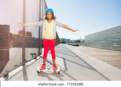 African girl riding hoverboard on the side walk