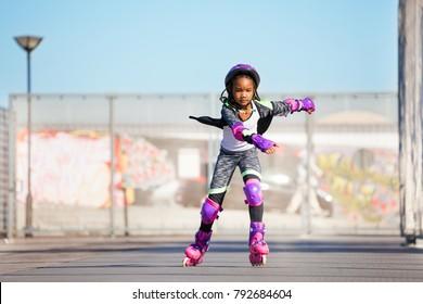 African girl rollerblading fast at skate park