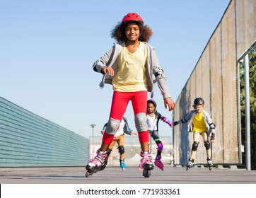 African girl rollerblading with friends at stadium