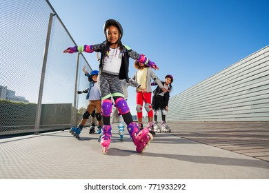 African girl rollerblading with hands like wings