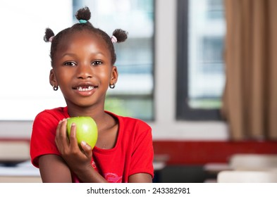 African girl at school desk ready to eat her apple.