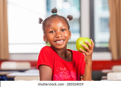 African girl at school holding green apple fruit.