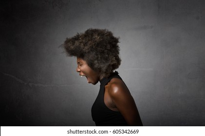 african girl screaming in lateral view, dark background