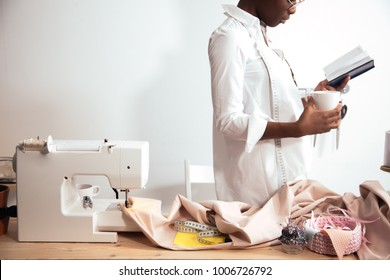 african girl seamstress making notes at notebook. Fashion designer drawing sketches