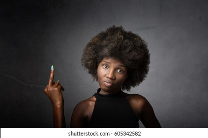 african girl showing middle finger, dark background