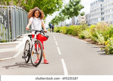 African girl standing with bicycle at city park