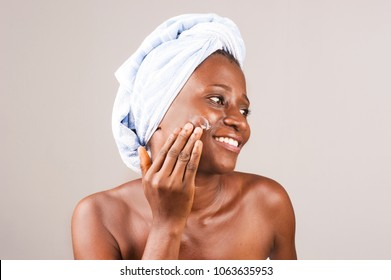 African girl standing on gray background with bath towel tied on her head chewing cream on cheek smiling.