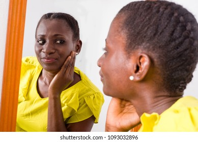 African girl standing in yellow tank looking at herself in a mirror smiling.
