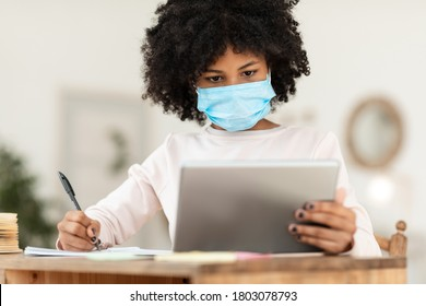 African Girl With Tablet Learning Online Wearing Mask Sitting At Desk At Home. Virus Protection At School. Selective Focus