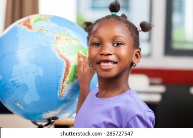 African girl touching world globe at school.