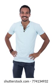 African goatee man with hands at the waist, wearing a light blue t-shirt, jeans and bracelet. Isolated on white background.