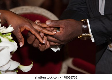 African groom put the wedding ring on bride