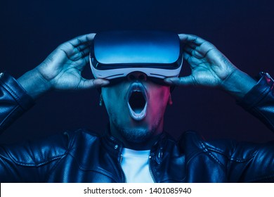 African guy amazed with what he sees in virtual reality glasses, mouth wide open and says WOW