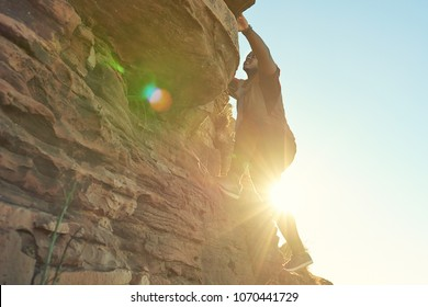 African guy climbing a near vertical rock face with clear blue skies and flare from the sun shining through from behind the climber.
