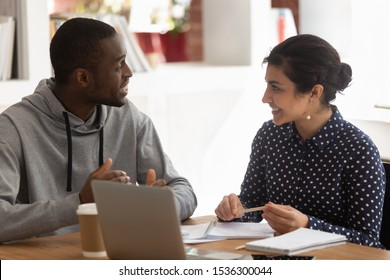 African guy indian girl diverse classmates sitting at classroom desk having common task, talking about work exercise to do concept of communication teamwork at studying process, multiracial friendship