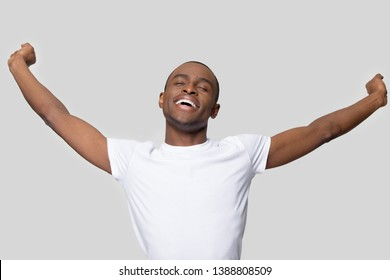 African guy isolate on grey wall wearing white t-shirt awake up having free time, accomplish work or study, feels rested delighted and satisfied breathing enjoying fresh air, starting new day concept