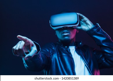 African guy pointing forward with finger while exploring virtual reality, pictured in darkness with neon light