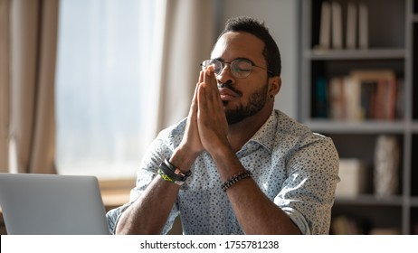 African guy sit at desk with clasped palms closed eyes thinking search problem solution, collect thoughts together, organize his emotional state before important meeting. Prayer hands sign of ask help