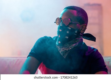 African guy in sunglasses, t-shirt and black bandana on face sitting on couch in the room with smoke around and looking forwards