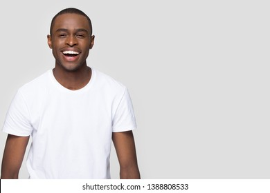 African guy in t-shirt look at camera laughing having ultra white toothy smile pose aside isolate on grey wall copy space for your advertisement text, dental orthodontic products and services concept