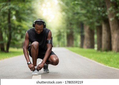 African guy tying laces on his sneakers before jogging at park, empty space