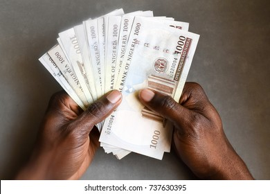 African hand man holding one thousand Naira Nigerian spread fan isolated on dark background