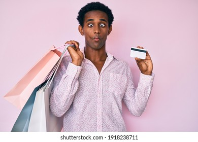 African handsome man holding shopping bags and credit card making fish face with mouth and squinting eyes, crazy and comical.