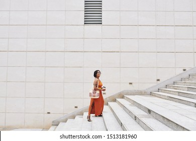 African happy woman in elegant orange dress holding coffee drink and moving up the stairs in the city