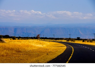 african highway route photographed on the way to the african safari national park serengeti in tanzania with great colors and contrasts between the yellow grassland, the dark road and the mountains