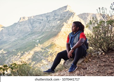 African hiker taking a break sitting next to the hiking trail on a mountainous trail to take in the amazing views of all the mountains around him that surround the amazing city scape.