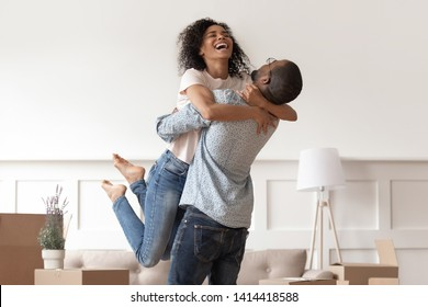 African husband lifting happy wife laughing celebrating moving day with boxes, excited first time home buyers renters owners having fun enjoy relocation into own new flat house, mortgage investment