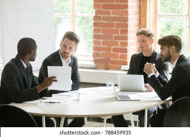 African investment advisor consulting diverse businessmen, partners listening to black consultant holding showing document, making offer, presenting project plan at corporate executive team meeting